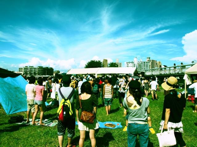 芝生広場で背中を向けている人々