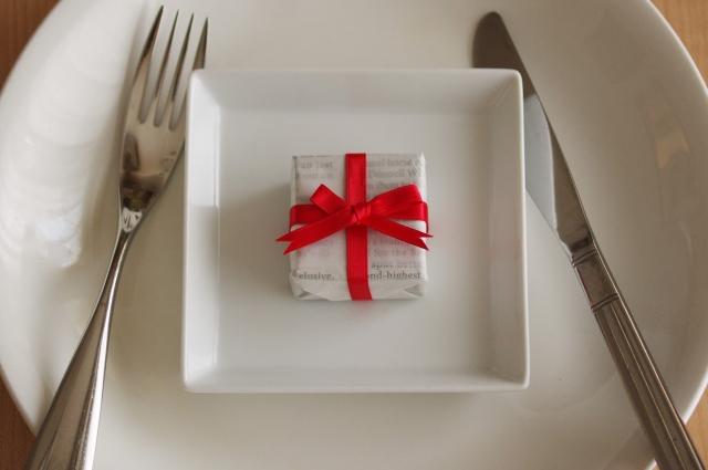 皿に乗った赤いリボンのプレゼントとナイフとフォーク