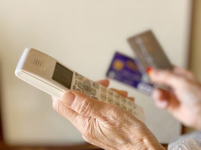 受話器とクレジットカードを持つ老人の手