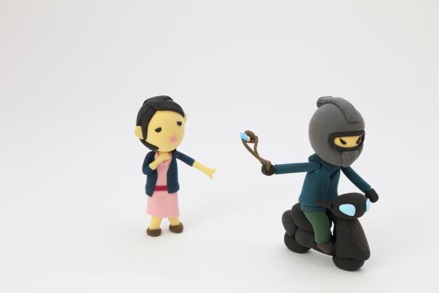 バイクに乗った男性とバッグを取られる女性