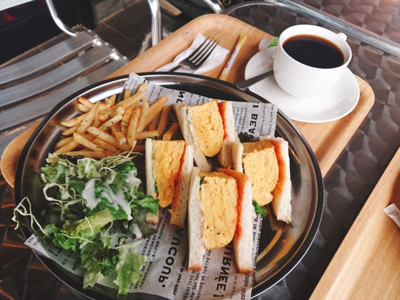 丸い皿の上の卵サンドとコーヒー