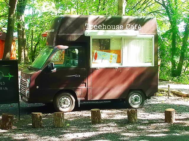 茶色いキッチンカーと林