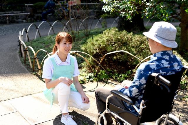 女性の介護職員と車いすに乗った老人