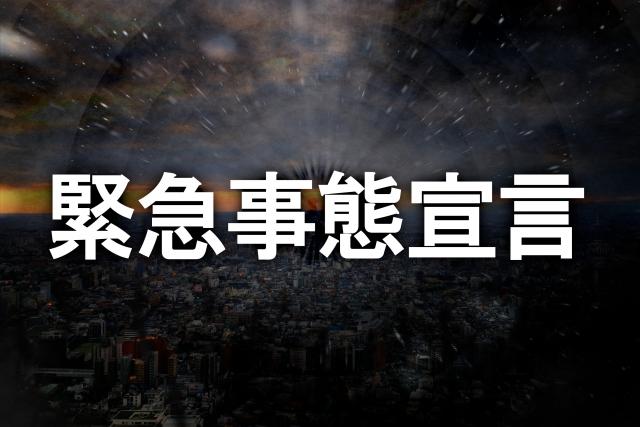 黒い空に、白地の緊急事態宣の文字言の